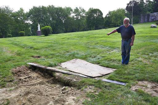 "This Thursday Aug. 10, 2017 photo shows Mount Holiness Memorial Park caretaker Bill Plog as he stands by the burial plot of Cleveland Butler, in Butler, N.J. The New York Daily News reported the burial uncovered a moldering foot of a neighboring corpse that fell on top of Butler's coffin during the eulogy on Aug. 4, 2017. Plog said it's unfortunate that it happened, ""but this is a graveyard."" (James Keivom/The Daily News via AP)"