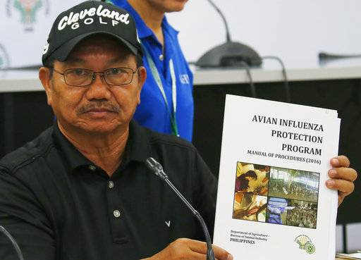Department of Agriculture Secretary Emmanuel Pinol holds a manual for Avian Influenza Protection during a news conference on the confirmation of the first bird flu case in the country Friday, Aug. 11, 2017 in Manila, Philippines. Pinol said the Philippines will cull at least 400,000 birds after confirming its first bird flu outbreak, but that no animal-to-human transmission has been reported. (AP Photo/Bullit Marquez)