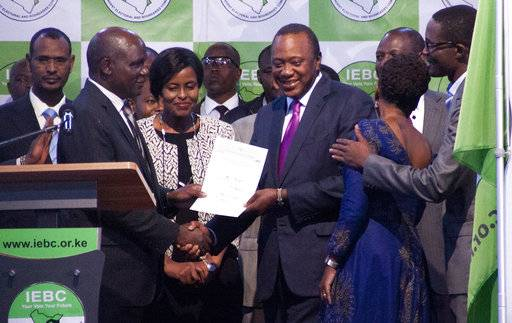 "The Chairman of the Independence Electoral and Boundaries Commission, Wafula Chebukati , left, hands over the certificate to Uhuru Kenyatta, centre right, after announcing him the winner in the presidentail race at the Centre in Bomas, Nairobi, Kenya, Friday, Aug.11, 2017. The commission said Kenyatta won Tuesday's election with 54 percent of the vote. It called the vote ""credible, fair and peaceful."" (AP Photo/ Sayyid Abdul Azim)"