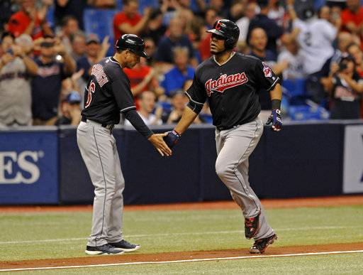 Cleveland Indians third base coach Mike Sarbaugh, left, congratulates Edwin Encarnacion after his solo home run off Tampa Bay Rays starter Jake Faria during the fifth inning of a baseball game Friday, Aug. 11, 2017, in St. Petersburg, Fla.