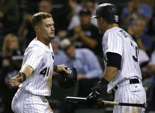 Chicago White Sox's Adam Engel, left, celebrates with Nicky Delmonico after scoring on a sacrifice bunt by Yolmer Sanchez during the seventh inning of a baseball game against the Kansas City Royals, Friday, Aug. 11, 2017, in Chicago. (AP Photo/Nam Y. Huh)