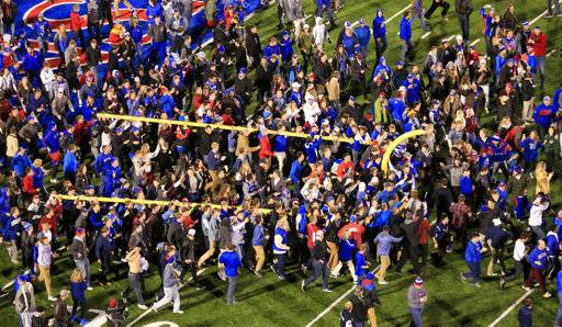 FILE - In this Nov. 19, 2016, file photo, Kansas fans tear down the goal posts after defeating Texas in overtime of an NCAA college football game in Lawrence, Kan. The Jayhawks had lost 19 straight Big 12 games when Texas rolled into town. They hadn't beaten the Longhorns since 1938, and trailed 21-10 in the fourth quarter. But a spirited comeback forced overtime, and a field goal gave them just their second conference victory in 29 tries. It was the highlight of a 2-10 season _ and a crucial building block for the future. (AP Photo/Orlin Wagner, File)