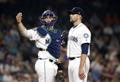 Seattle Mariners catcher Mike Zunino, left, signals to the dugout as starting pitcher James Paxton waits on the mound during the seventh inning of the team's baseball against the Los Angeles Angels on Thursday, Aug. 10, 2017, in Seattle. Paxton was checked by a trainer and left the game. (AP Photo/Elaine Thompson)