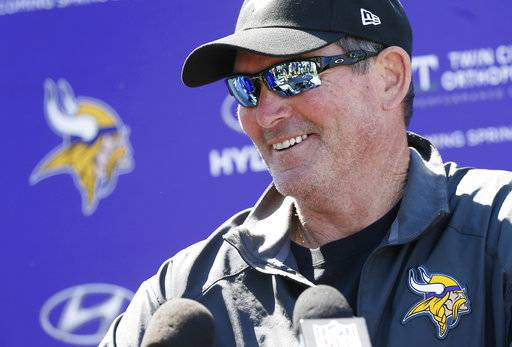 FILE - In this June 6, 2017, file photo, Minnesota Vikings head coach Mike Zimmer talks with reporters after an NFL football team practice in Eden Prairie, Minn. After last season fell apart for Zimmer and the Vikings, the hard-nosed head coach has returned for a crossroad year four with optimism that his eye trouble is behind him and a greater sense of trust in those around. (AP Photo/Jim Mone, File)