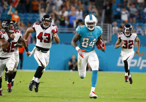 Miami Dolphins wide receiver Damore'ea Stringfellow (84) runs for a touchdown ahead of Atlanta Falcons linebacker Jack Lynn (43), cornerback Jalen Collins (32) and defensive back Marcelis Branch (35), during the second half of an NFL preseason football game, Thursday, Aug. 10, 2017, in Miami Gardens, Fla. (AP Photo/Wilfredo Lee)