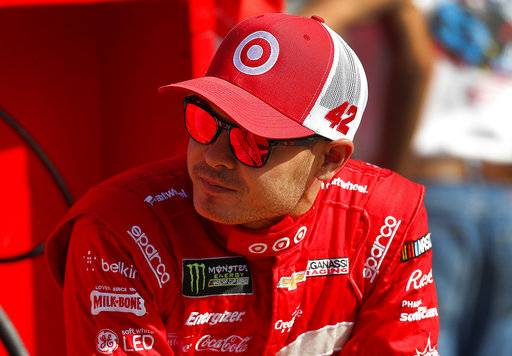 Kyle Larson talks with teammates prior to qualifying for the NASCAR Cup Series auto race in Brooklyn, Mich., Friday, Aug. 11, 2017. (AP Photo/Paul Sancya)