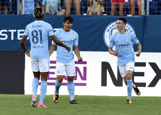 FILE - In this Saturday, July 29, 2017 file photo, Manchester City's Brahim Diaz, center, celebrates with teammates Demean Duhaney, left, and Phil Foden after scoring a goal against Tottenham Hotspur during an International Champions Cup match in Nashville, Tenn. The leap from City's academy to the star-filled first team has proved to be too big for most, but Foden appears good enough to make the transition. The diminutive 17-year-old midfielder impressed coach Pep Guardiola with his passing and technical qualities during City's tour to the United States in July and is set to be part of the senior squad for the coming season (AP Photo/Mark Zaleski, file)