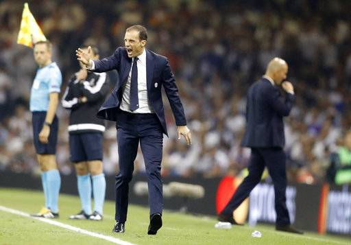 FILE - In this photo taken on June 3, 2017, Juventus head coach Massimiliano Allegri shouts as Real Madrid's head coach Zinedine Zidane walks behind during the Champions League final soccer match between Juventus and Real Madrid at the Millennium stadium in Cardiff, Wales . After a tumultuous two months, Juventus is looking to get back to what it does best: winning trophies. (AP Photo/Frank Augstein)