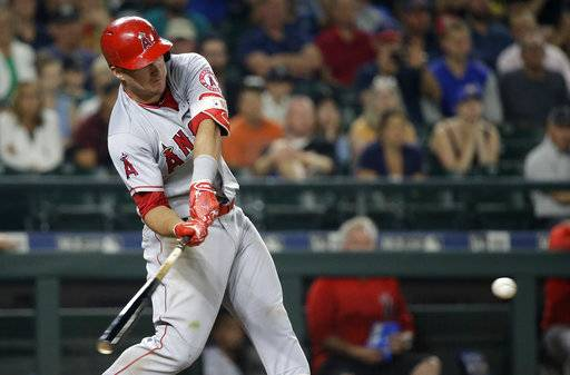 Los Angeles Angels' Mike Trout swings for a three-run double against the Seattle Mariners during the ninth inning of a baseball game Thursday, Aug. 10, 2017, in Seattle. (AP Photo/Elaine Thompson)