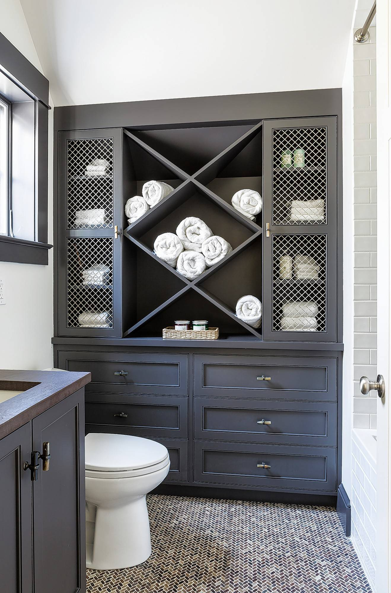 Take advantage of the vertical space in a small bathroom, designer Shazalynn Cavin-Winfrey says. A tall cabinet or a medicine cabinet over the toilet can make a big difference.