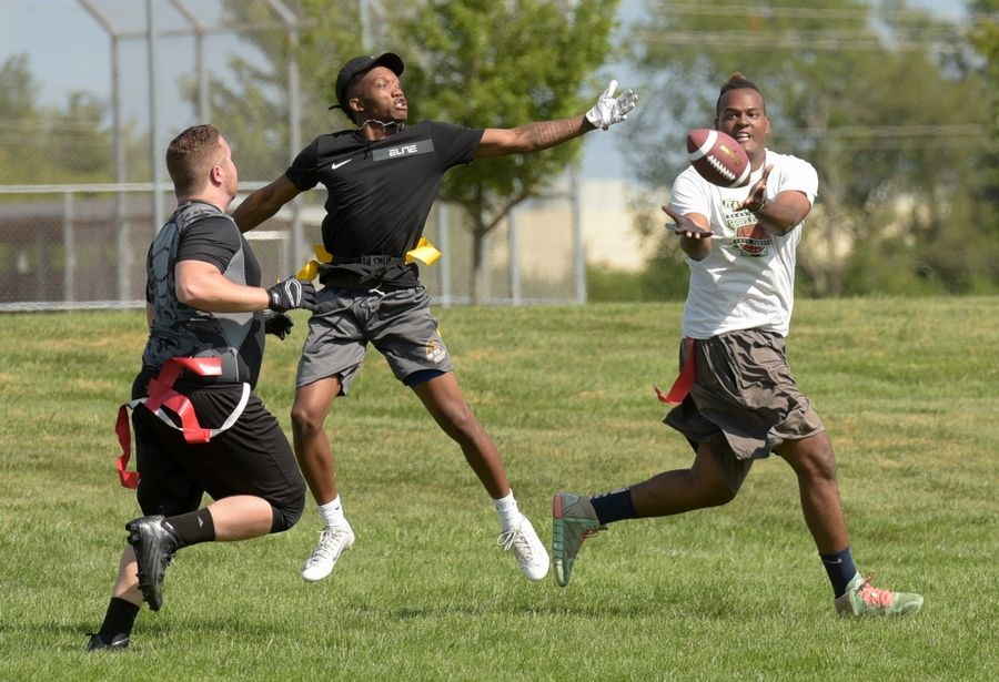 Tamar Elerby of Aurora, right, catches a pass during a flag football game during the Unity Partnership backyard party Saturday at Metea Valley High School. The group aims to bridge gaps between police and the communities.