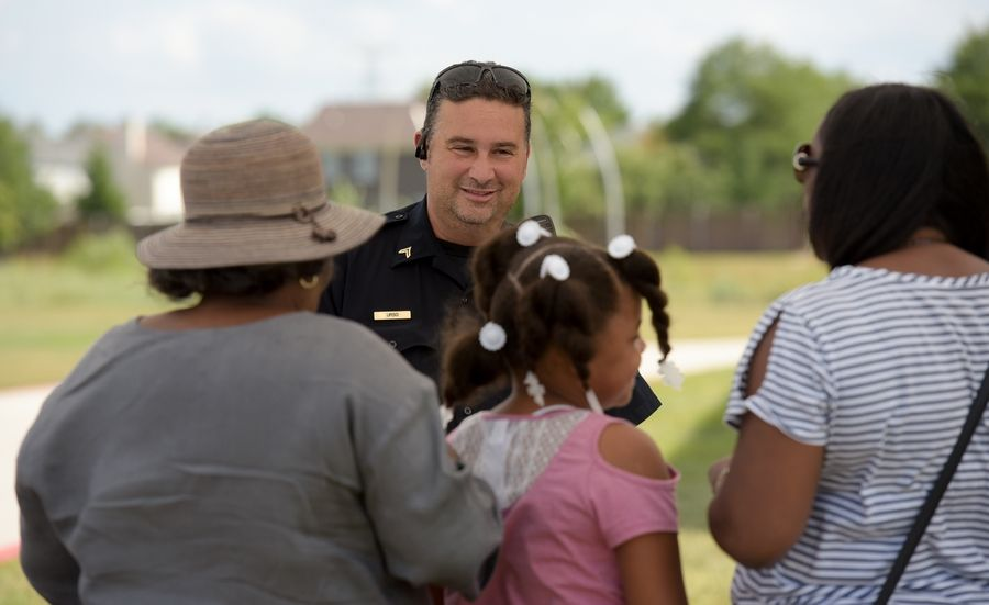 DuPage County Sheriff Deputy Mike Urso talks with a visitor to the Unity Partnership backyard party Saturday at Metea Valley High School.