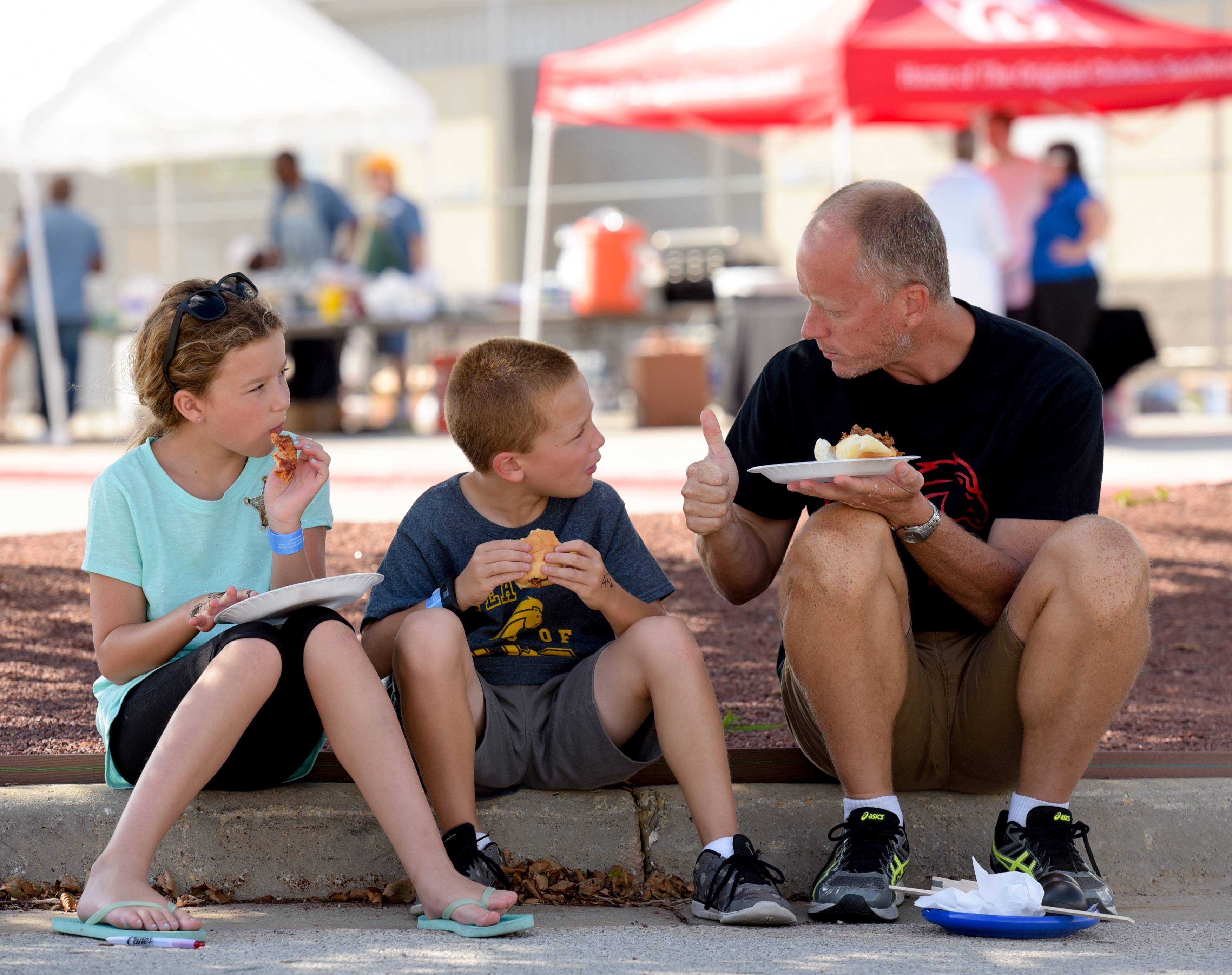 Sasha, 10, Ari, 8, and Don Pankuch of Oswego enjoy food during the Unity Partnership backyard party Saturday at Metea Valley High School.