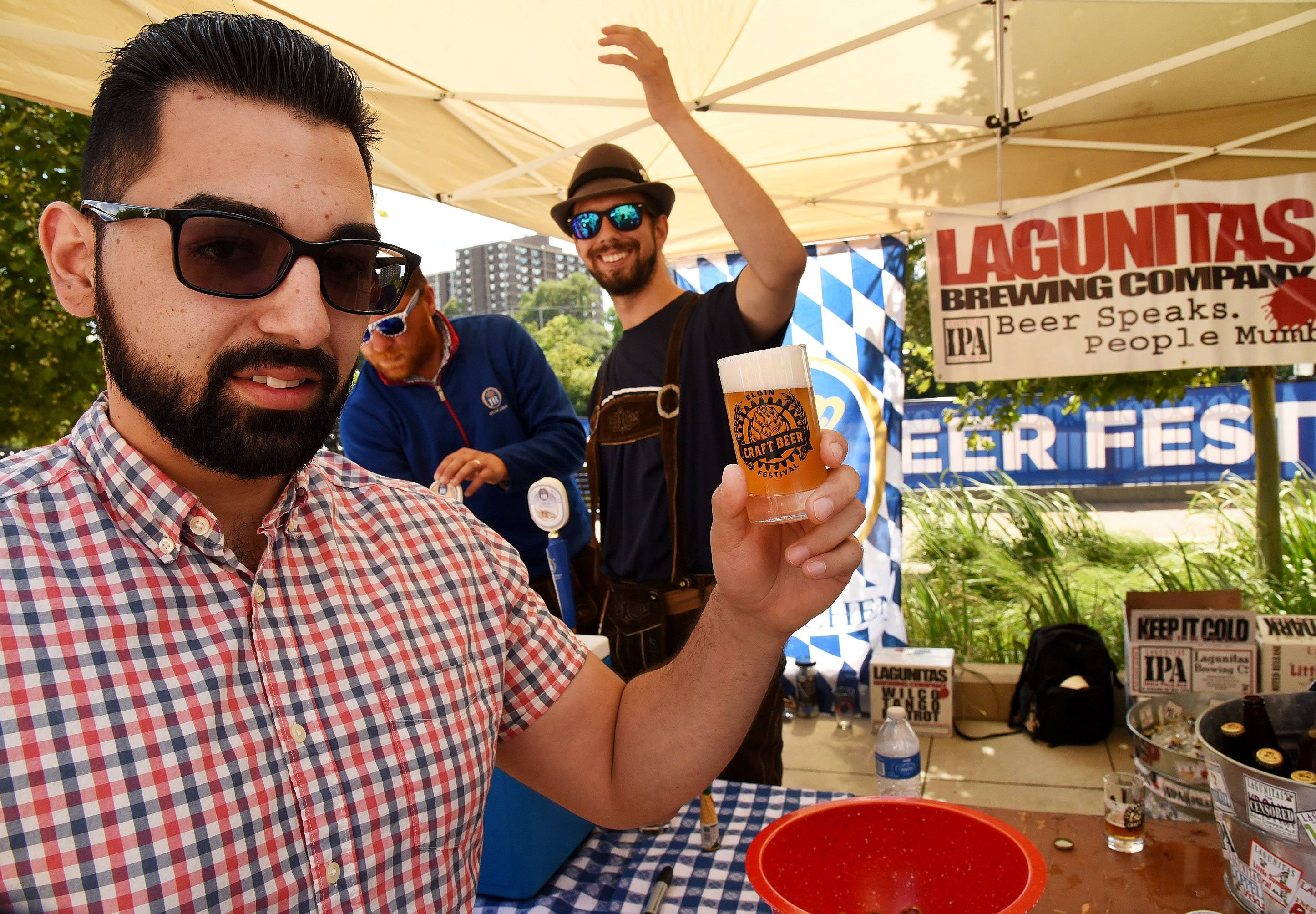 Ernesto Aranda of Elgin holds up a beer that Chris Pacanowski, right, just poured for him from the Hoffman Estates Beer Garden at the Elgin Craft Beer Festival Saturday.
