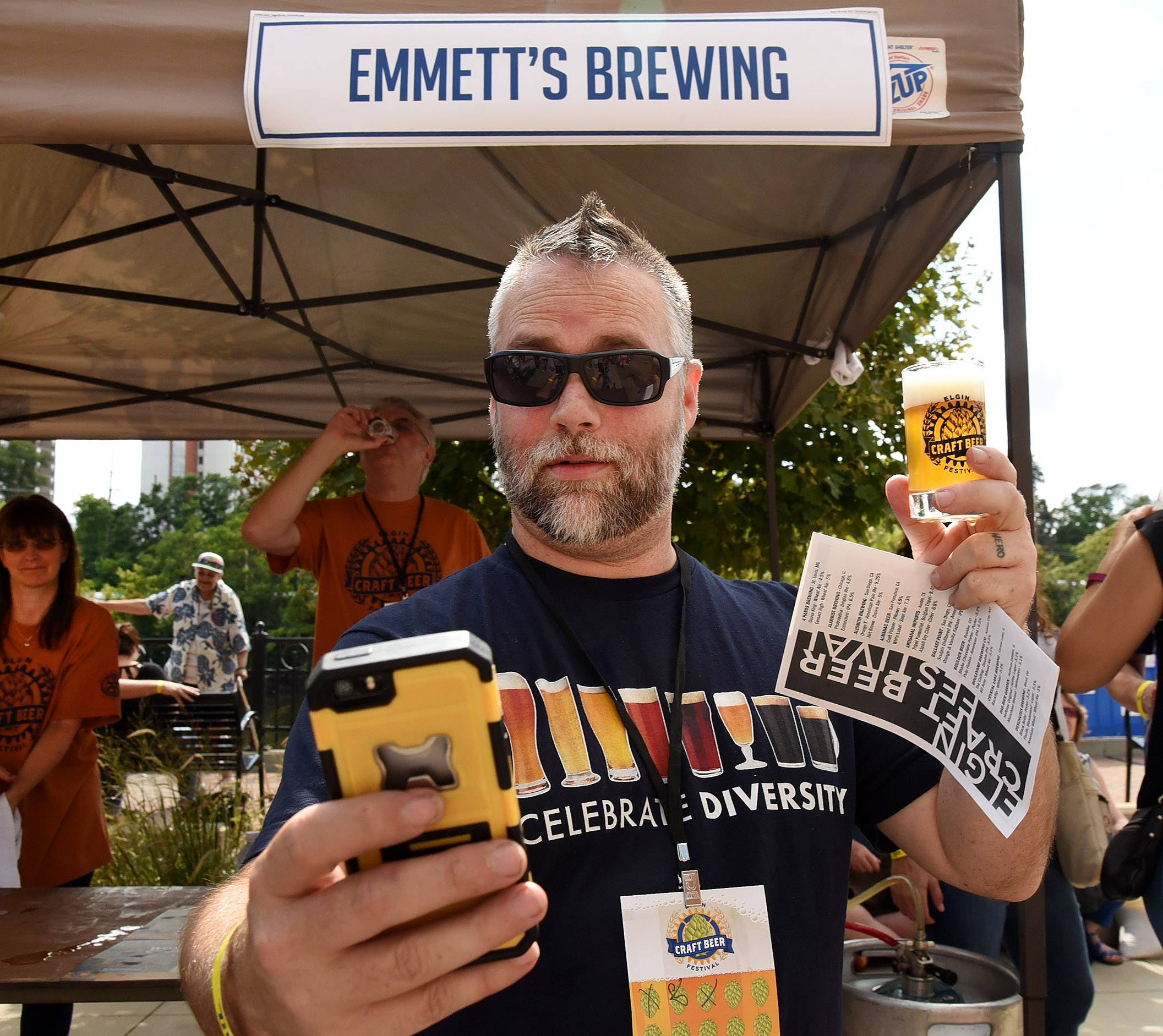 Nick Thomason of Dallas tries for a selfie with Emmett's Brewing of Palatine while visiting friends in Elgin during the Elgin Craft Beer Festival Saturday.