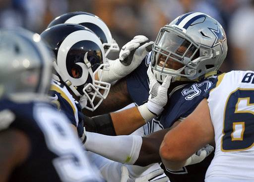 Dallas Cowboys defensive end Taco Charlton, right, gets a hand to the mask from the Los Angeles Rams offensive guard Cody Wichmann during the first half of a preseason NFL football game Saturday, Aug. 12, 2017, in Los Angeles.