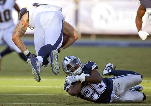 Dallas Cowboys defensive back Duke Thomas, below right, cannot reach Los Angeles Rams tight end Tyler Higbee, left, who dives forward before being tackled during the first half of a preseason NFL football game Saturday, Aug. 12, 2017, in Los Angeles.