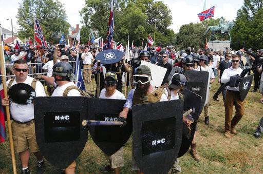 White nationalist demonstrators hold their ground as they clash with counter demonstrators in Lee Park in Charlottesville, Va., Saturday, Aug. 12, 2017.  Hundreds of people chanted, threw punches, hurled water bottles and unleashed chemical sprays on each other Saturday after violence erupted at a white nationalist rally in Virginia. At least one person was arrested.