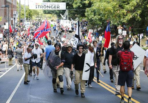 White nationalist demonstrators walk through town after their rally was declared illegal near Lee Park in Charlottesville, Va., Saturday, Aug. 12, 2017.