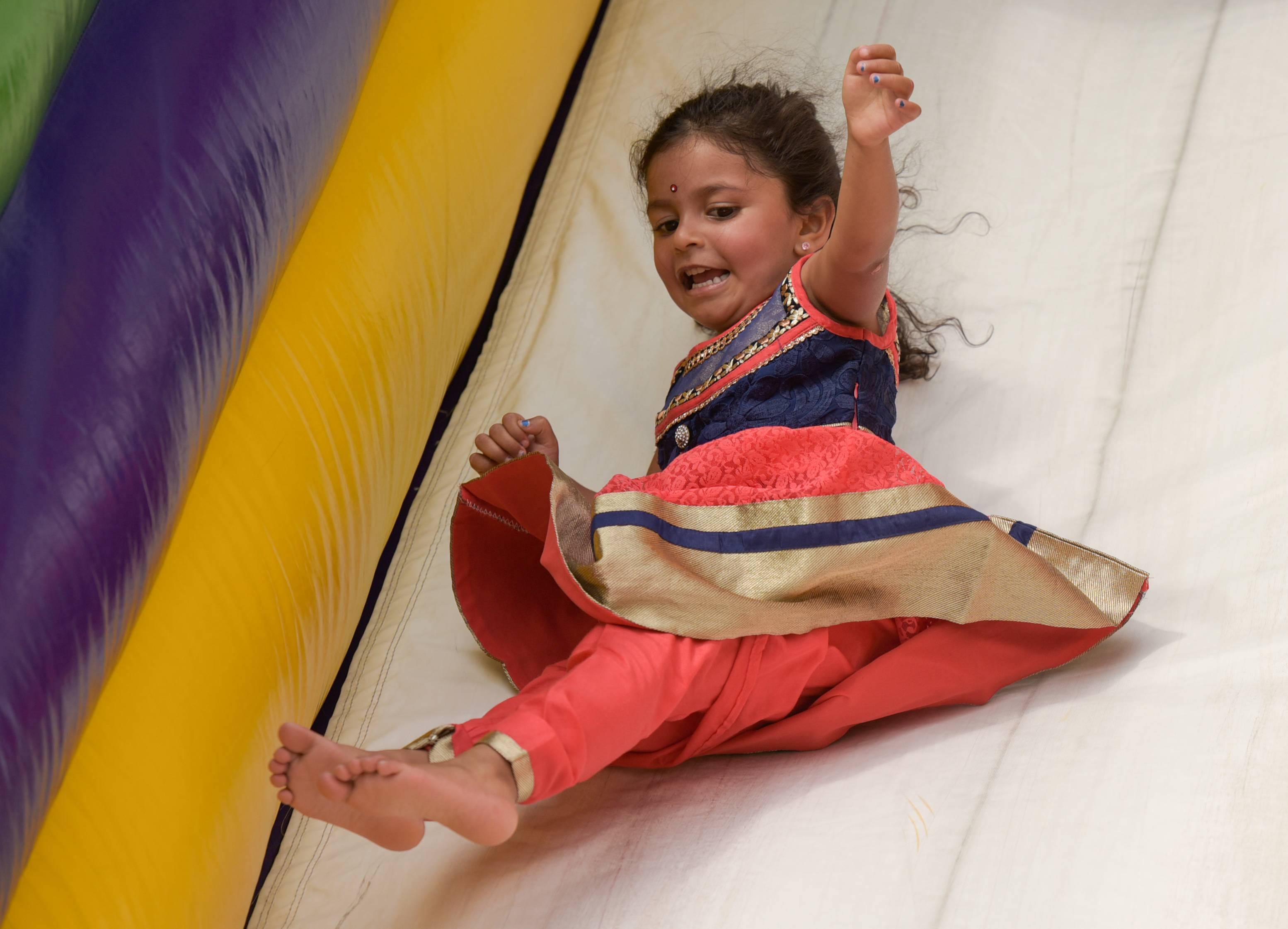 Aaradhya Bhagat, 3, of Naperville enjoys a fun slide Sunday during the third annual India Day Festival in Naperville.