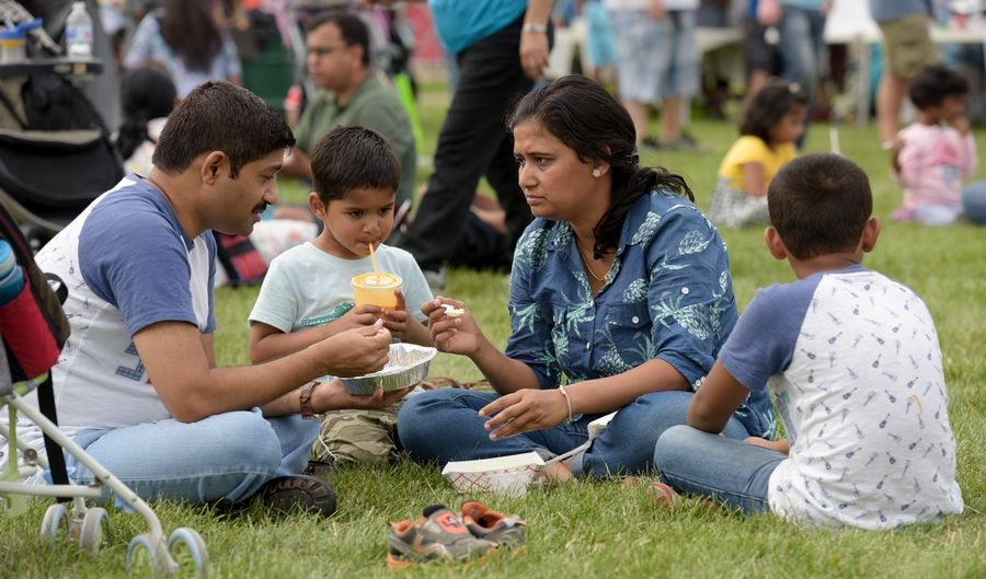 The Diver family -- Mahadev, 3-year-old Vihan, Manisha and 6-year-old Virag, all of Lombard -- enjoy a meal Sunday at the third annual India Day Parade and Festival in Naperville.