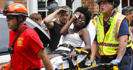Rescue personnel help an injured woman after a car ran into a large group of protesters after an white nationalist rally in Charlottesville, Va., Saturday, Aug. 12, 2017.  The nationalists were holding the rally to protest plans by the city of Charlottesville to remove a statue of Confederate Gen. Robert E. Lee. There were several hundred protesters marching in a long line when the car drove into a group of them.