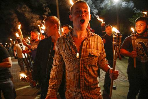 In this photo taken Friday, Aug. 11, 2017, multiple white nationalist groups march with torches through the UVA campus in Charlottesville, Va.   Hundreds of people chanted, threw punches, hurled water bottles and unleashed chemical sprays on each other Saturday after violence erupted at a white nationalist rally in Virginia.  (Mykal McEldowney/The Indianapolis Star via AP)