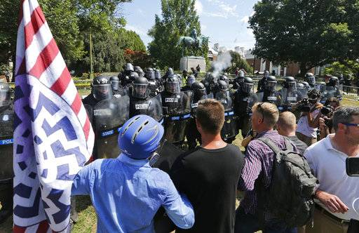White nationalist demonstrators hold their ground against Virginia State Police as police fire tear gas rounds in Lee Park in Charlottesville, Va., Saturday, Aug. 12, 2017.  Gov. Terry McAuliffe declared a state of emergency and police dressed in riot gear ordered people to disperse after chaotic violent clashes between white nationalists and counter protestors.