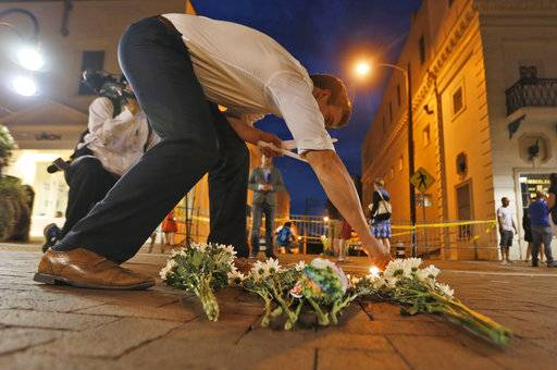 Charlottesville resident Elliot Harding lights a candle as he places flowers and a stuffed animal at a makeshift memorial for the victims after a car plowed into a crowd of people peacefully protesting a white nationalist rally earlier in the day in Charlottesville, Va., Saturday, Aug. 12, 2017.