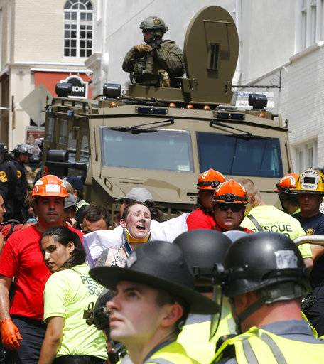 Rescue personnel help injured people after a car ran into a large group of protesters after an white nationalist rally in Charlottesville, Va., Saturday, Aug. 12, 2017. The nationalists were holding the rally to protest plans by the city of Charlottesville to remove a statue of Confederate Gen. Robert E. Lee. There were several hundred protesters marching in a long line when the car drove into a group of them.