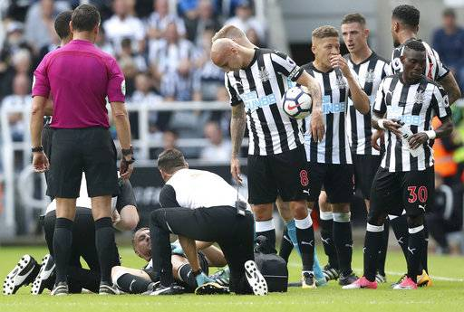 Newcastle United's Florian Lejeune received medical attention on the pitch during the English Premier League soccer match against Tottenham Hotspur at St James' Park, Newcastle, England, Sunday, Aug. 13, 2017. (Owen Humphreys/PA via AP)