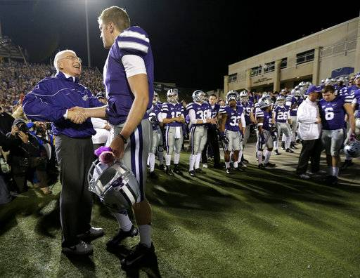 FILE - In this Dec. 1, 2012, file photo, Kansas State coach Bill Snyder, left, talks to quarterback Collin Klein during a senior day recognition before an NCAA college football game against Texas, in Manhattan, Kan. Kansas State coach Bill Snyder is back for another season, despite a cancer scare earlier this year. The 77-year-old coach believes he has a team capable of contending for a Big 12 title and even a national championship, and no amount of chemotherapy was going to keep him from leading the Wildcats for the 26th year.