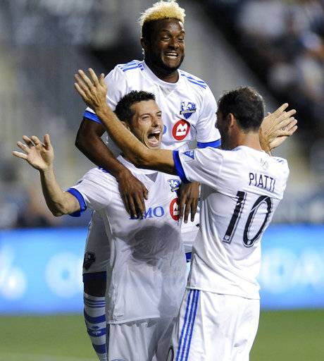 Montreal Impact's Blerim Dzemaili, middle, celebrates with Ignacio Patti, right, and Michael Salazar after scoring a goal during the second half of an MLS soccer match against the Philadelphia Union on Saturday, Aug. 12, 2017, in Chester, Pa. The Impact won 3-0.