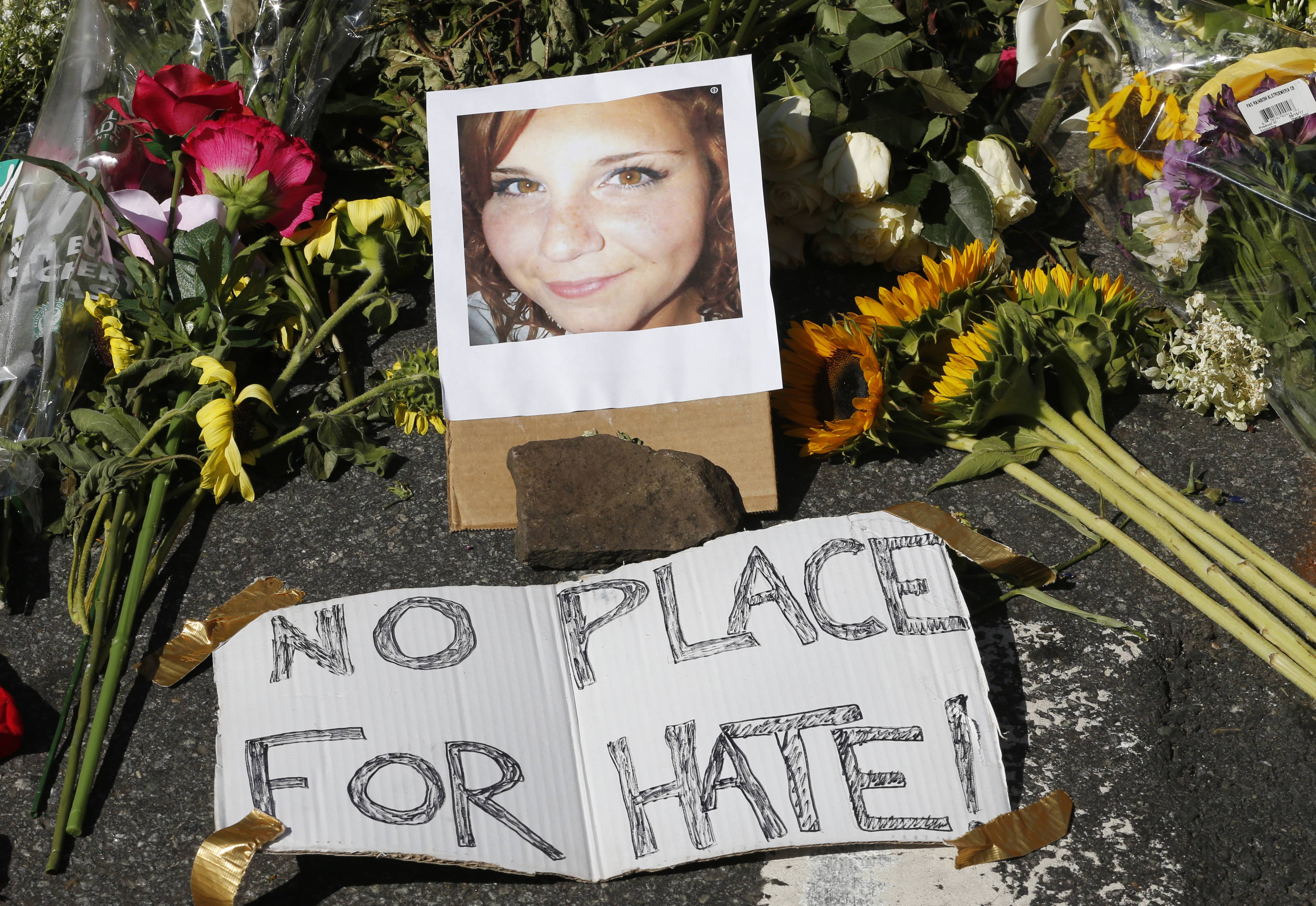 A makeshift memorial of flowers and a photo of victim Heather Heyer sits in Charlottesville, Virginia, Sunday. Heyer died when a car rammed into a group of people who were protesting the presence of white supremacists.