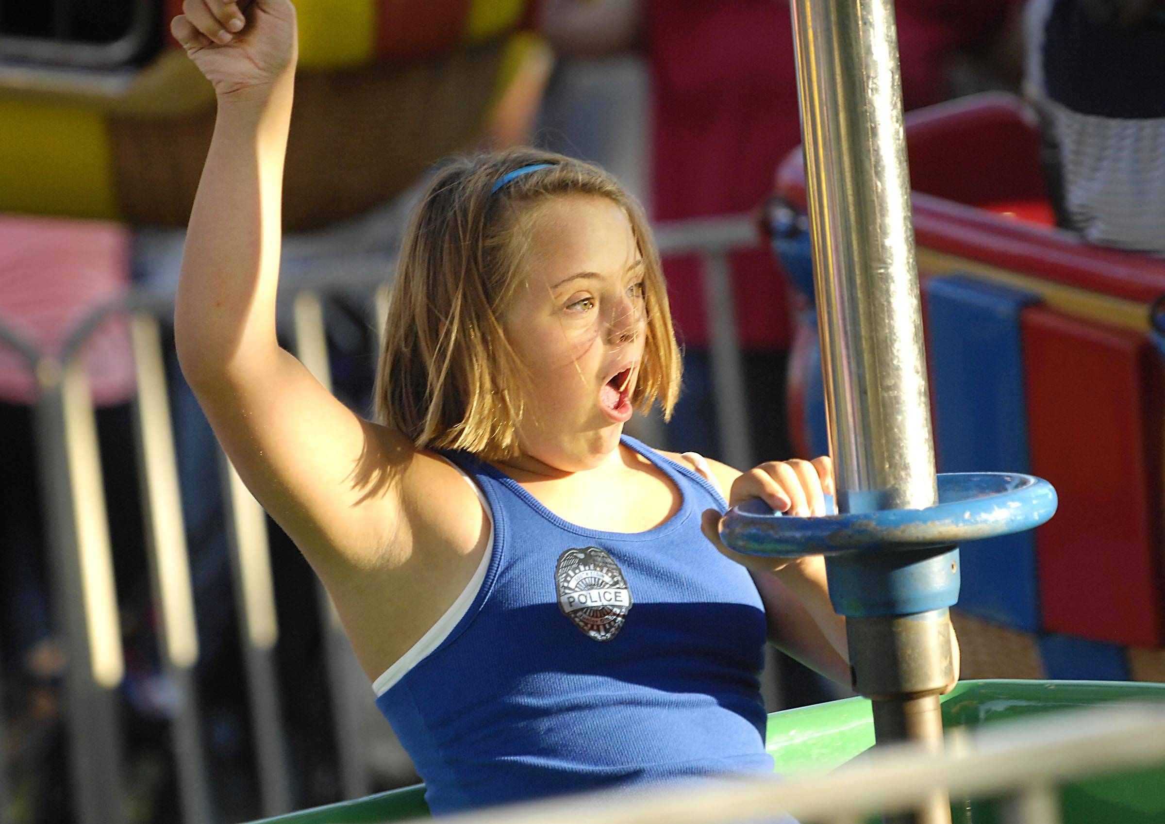 "Mari Landwehr, 12, of Geneva hoots it up as she spins on the ballon ride at a previous ""Special Night For Special Kids"" at the South Elgin Riverfest Express."