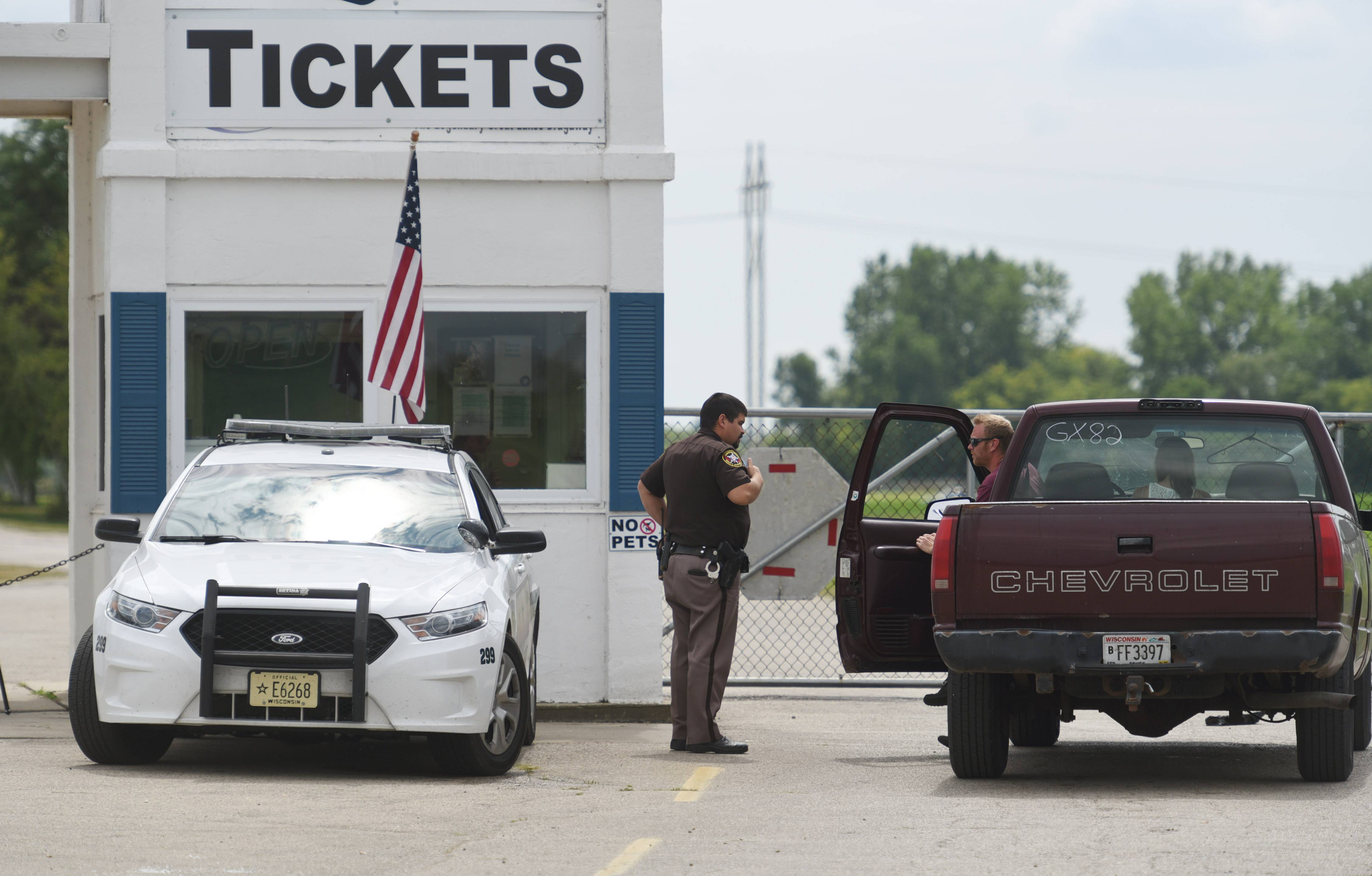 A Kenosha County sheriff's deputy monitors the entrance to Great Lakes Dragaway Monday in Union Grove, Wisconsin. Three men from Aurora, North Aurora and Oswego were fatally shot Sunday night in what is believed to be a gang-related, targeted killing.