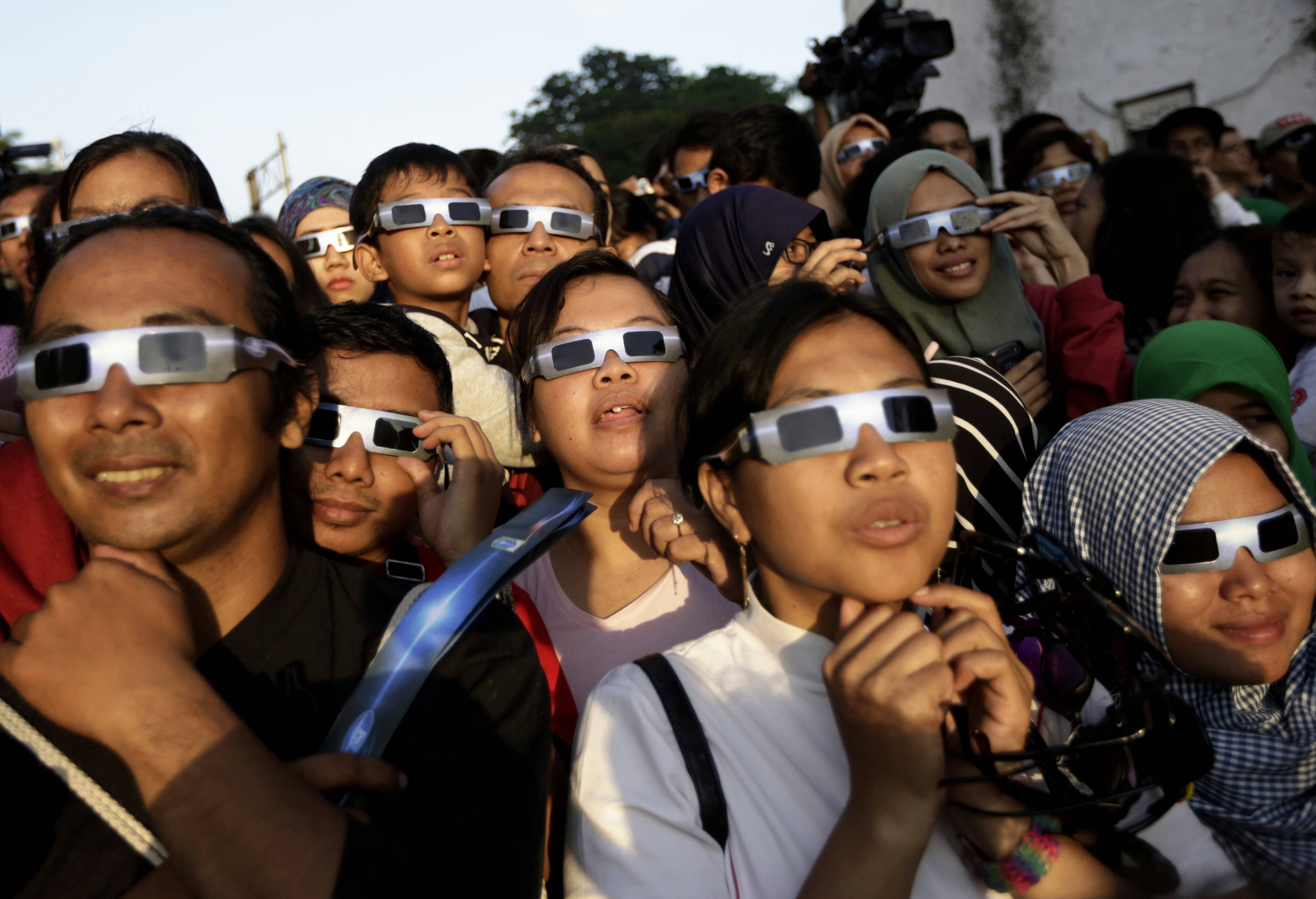People wearing protective glasses look up at the sun to watch a 2016 solar eclipse in Jakarta, Indonesia. Doctors say not to look at the sun without eclipse glasses or other certified filters except during the two minutes or so when the moon completely blots out the sun, called totality.