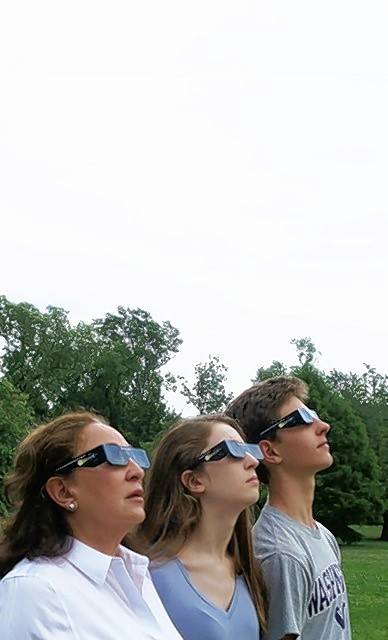 Patricia DePoli, left, Olivia Prendergast and Evan Prendergast try out their eclipse glasses before heading to southern Illinois next week.