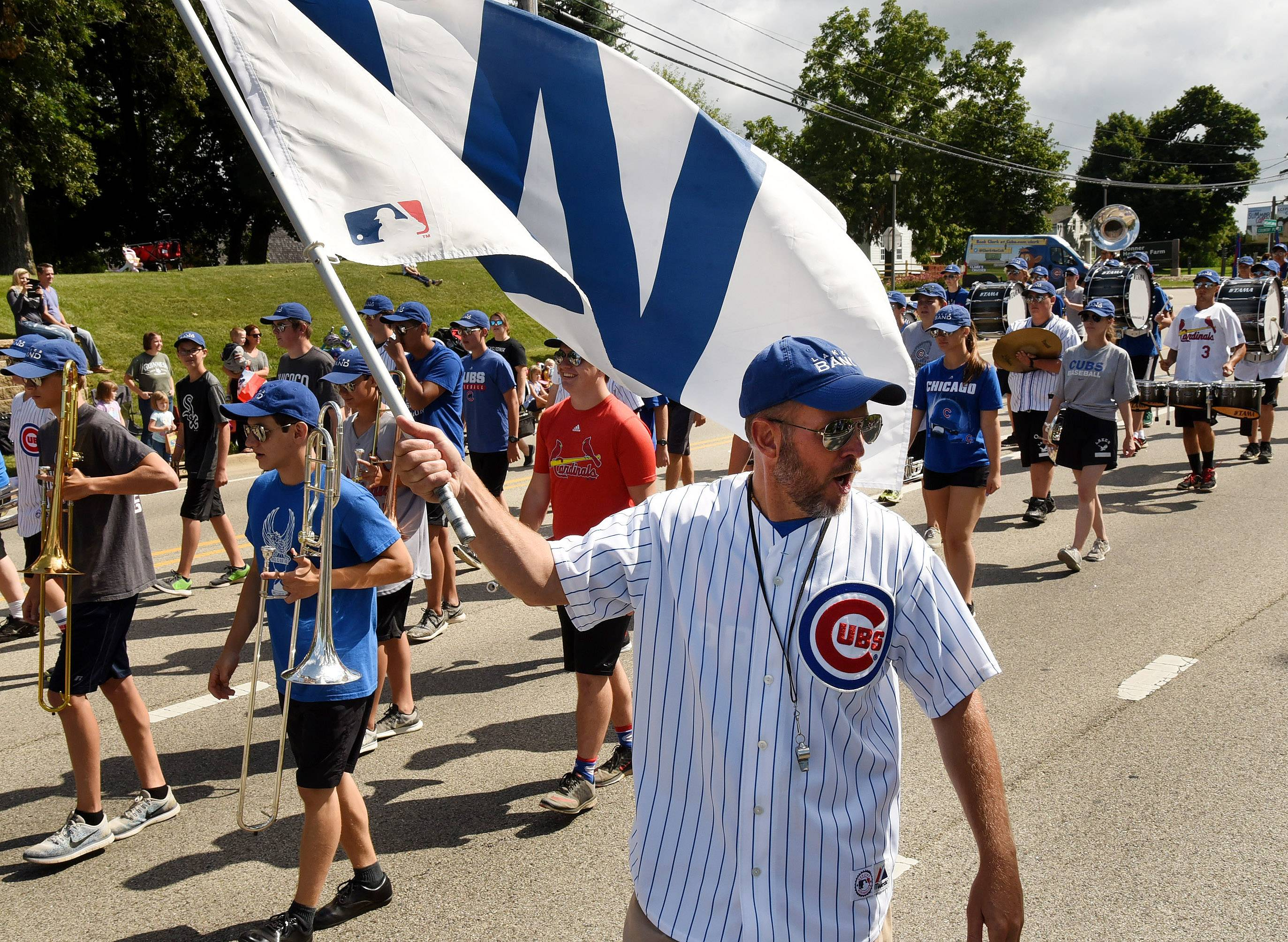 "Lakes High School Band Director Matt Kastor waves the W during the Lindenfest parade Saturday. The parade theme was ""Go Cubs Go."""
