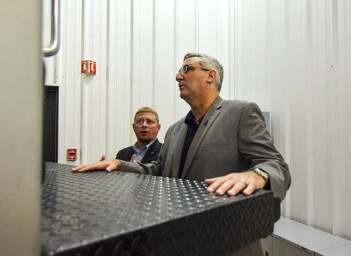 Great Dane Trailers plant manager Cory Lookebill, left, shows Gov. Eric Holcomb, right, the features of the trailers at the Brazil, Ind., plant on Monday. (Austen Leake /The Tribune-Star via AP)