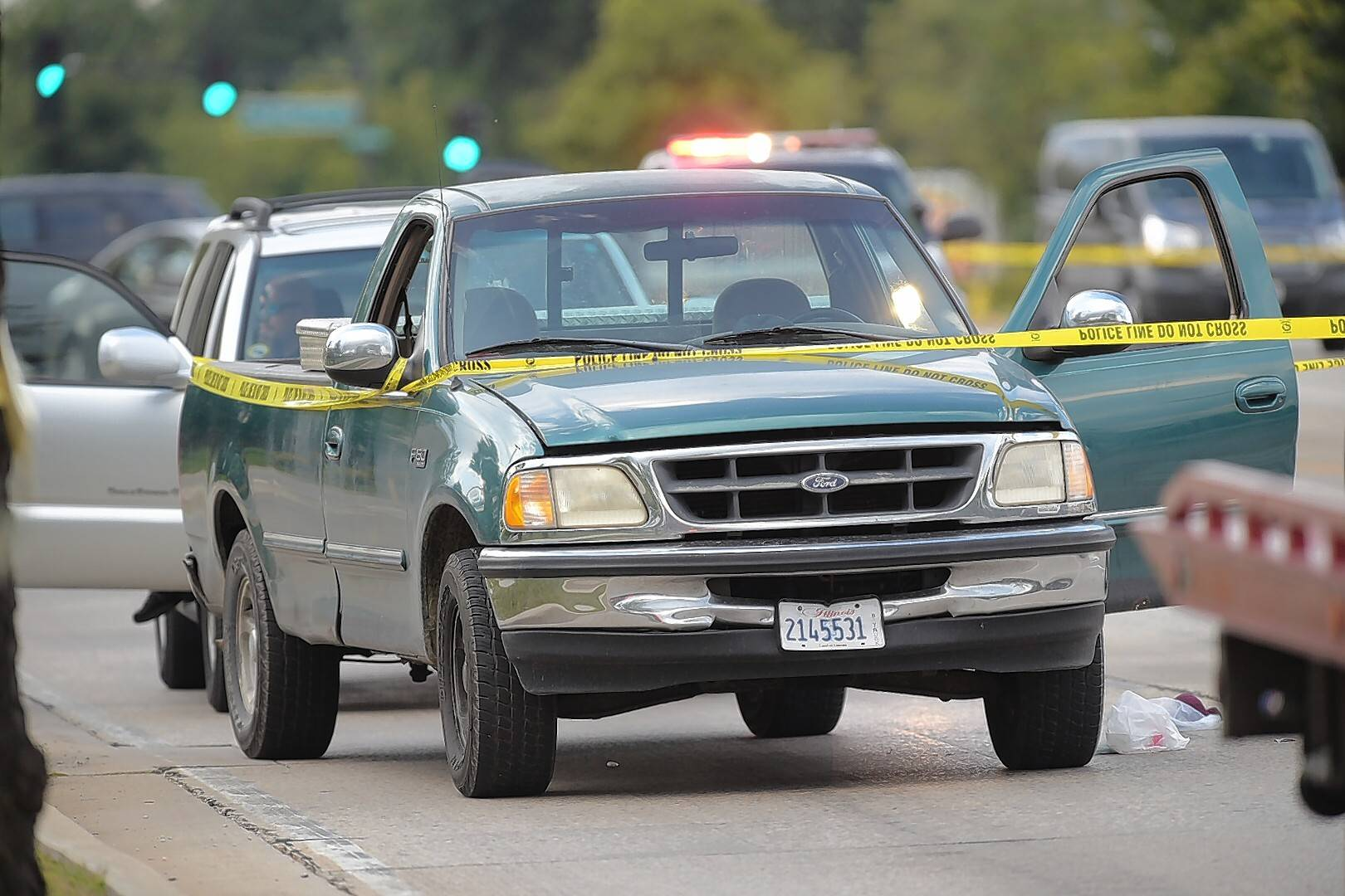 Mark Black/mblack@dailyherald.comYellow tape connected a pickup truck, an SUV and a police vehicle on Roselle Road near Wise Road in Schaumburg, as investigators worked the scene of a shooting Monday.