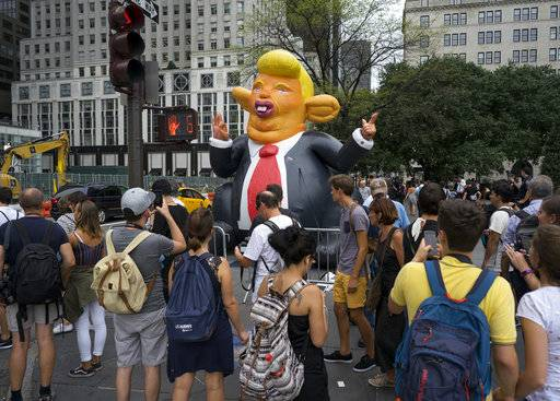 An inflatable caricature of President Donald Trump rises above pedestrians at W. 59th Street and 5th Ave. in New York Monday, Aug. 14, 2017, just three blocks north of Trump Tower. (AP Photo/Craig Ruttle)