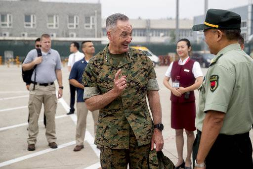 Joint Chiefs Chairman Gen. Joseph Dunford speaks with a Chinese official before boarding his plane at Beijing Capital International Airport in Beijing, China, Wednesday, Aug. 16, 2017, to travel to Shenyang, China to observe a Chinese Military Exercise. (AP Photo/Andrew Harnik)