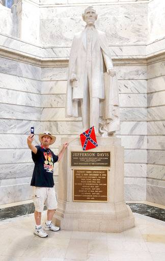 "This photo taken July 24, 2017, shows James Hendrickson, Corbin, Ky., taking a ""selfie"" with the Jefferson Davis Statue following a rally in support of keeping the statue of Confederate president Jefferson Davis in the Capitol, held on the steps of the State Capitol in Frankfort, Ky. The Kentucky chapter of the Sons of Confederate Veterans organized the rally. After the photo, he attached the flag to the statue. Kentucky's NAACP is renewing efforts to have the statue removed from the Capitol Rotunda in the aftermath of deadly violence in Charlottesville, Va. (Charles Bertram/Lexington Herald-Leader via AP)"