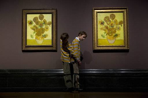 "FILE - In this Friday, Jan. 24, 2014 file photo, twins Edgar, left, and Gabriel, aged 10, arrange themselves to pose for photographers beside two versions of Dutch-born painter Vincent van Gogh's ""Sunflowers"", the left one from 1888 and the right one from 1889, during a photocall at the National Portrait Gallery in London. Five versions of a Vincent van Gogh masterpiece are being reunited for the first time in a ""virtual exhibition.� On Monday, Aug. 14, 2017, they will all be streamed to a global audience in a Facebook Live broadcast. (AP Photo/Matt Dunham, File)"