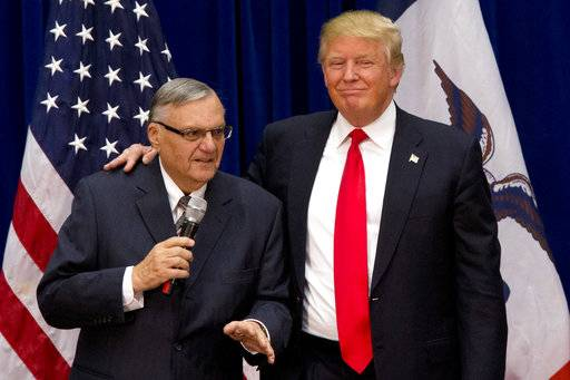 FILE - In this Jan. 26, 2016, photo, Republican presidential candidate Donald Trump is joined by Maricopa County, Ariz., Sheriff Joe Arpaio at a campaign event in Marshalltown, Iowa. President Trump says he may grant a pardon to former Sheriff Joe Arpaio following his recent conviction in federal court, prompting outrage among critics who say the move would amount to an endorsement of racism. (AP Photo/Mary Altaffer, File)