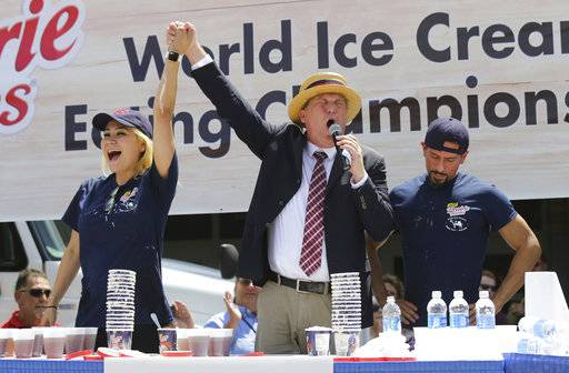 Major League Eating Emcee Sam Barclay, right, congratulates Miki Sudo, left, on setting a world record for eating the most pints of ice cream while second place eater Juan Rodriguez, right, recovers from the first-ever World Ice Cream Eating Championship at the Indiana State Fair in Indianapolis on Sunday, Aug. 13, 2017. (Michelle Pemberton/The Indianapolis Star via AP)