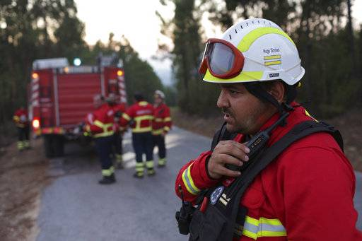 In this photo taken on Thursday, Aug. 10 2017, Hugo Simoes talks on the radio while coordinating a group of volunteer firefighters from Lisbon helping fight a forest fire near the village of Aldeia do Monte outside Abrantes, central Portugal. Almost all of the 2,000 Portuguese firefighters at a weeklong wildfire that killed more than 60 people this summer had something in common apart from the acute danger they faced: they were doing it for no pay and with equipment bought with public donations. More than 90 percent of Portugal's around 30,000 firefighters are volunteers. (AP Photo/Armando Franca)