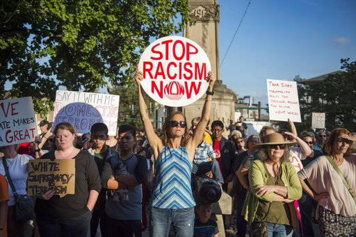 "Cathi Crabtree, center, holds her ""Stop Racism Now"" sign high during a rally at the Monroe County Courthouse in Bloomington, Ind., Sunday, Aug. 13, 2017. Protesters decrying hatred and racism converged around the country Sunday, the day after a white supremacist rally that spiraled into violence in Charlottesville, Va. (Chris Howell/The Herald-Times via AP)"