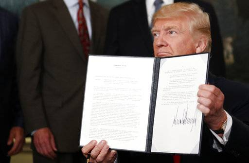 President Donald Trump holds up a signed memorandum calling for a trade investigation of China, Monday, Aug. 14, 2017, in the Diplomatic Reception Room of the White House in Washington. (AP Photo/Alex Brandon)